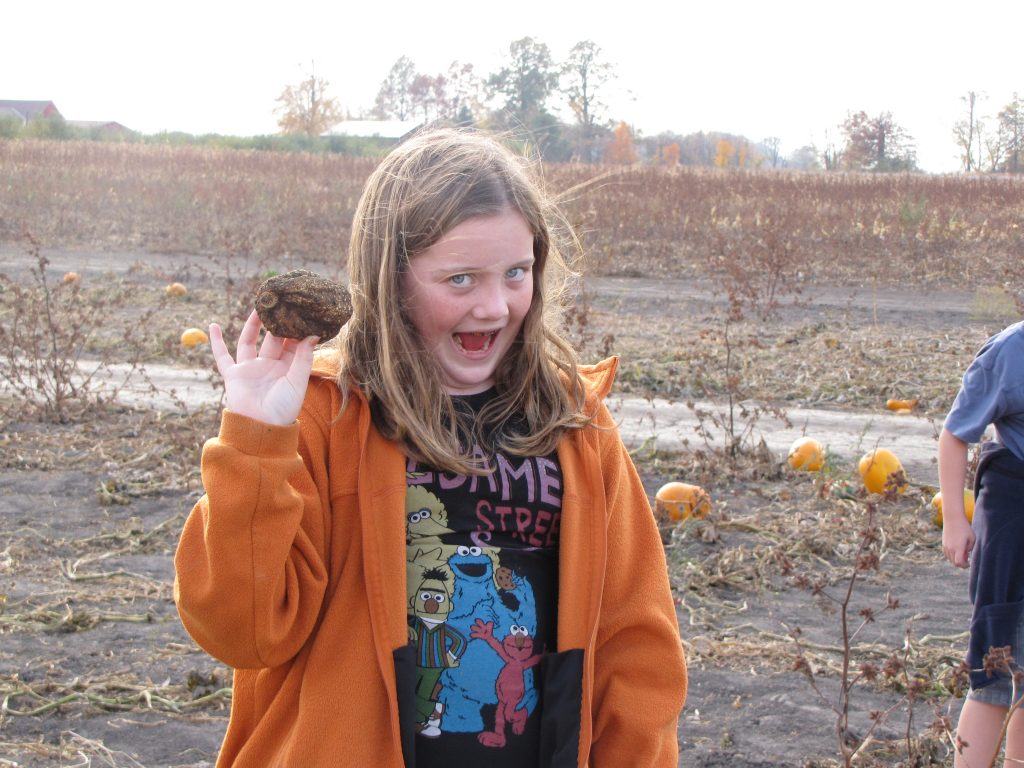 Mary Claire Holding Up a Rotten Pumpkin at the Pumpkin Patch
