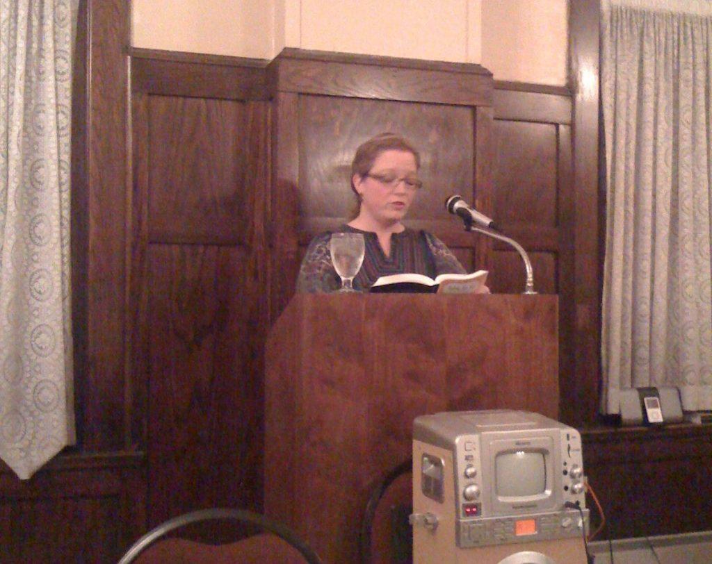 "Katrina Reading ""Table for Six"" at a Podium"