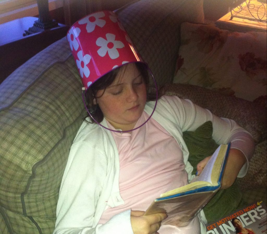 Mary Claire Wearing a Flowered Bucket on Her Head While Reading