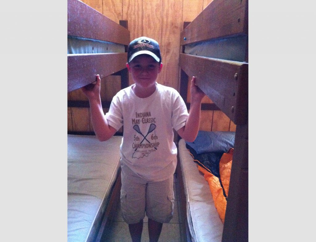 George Standing Between Bunks at Camp